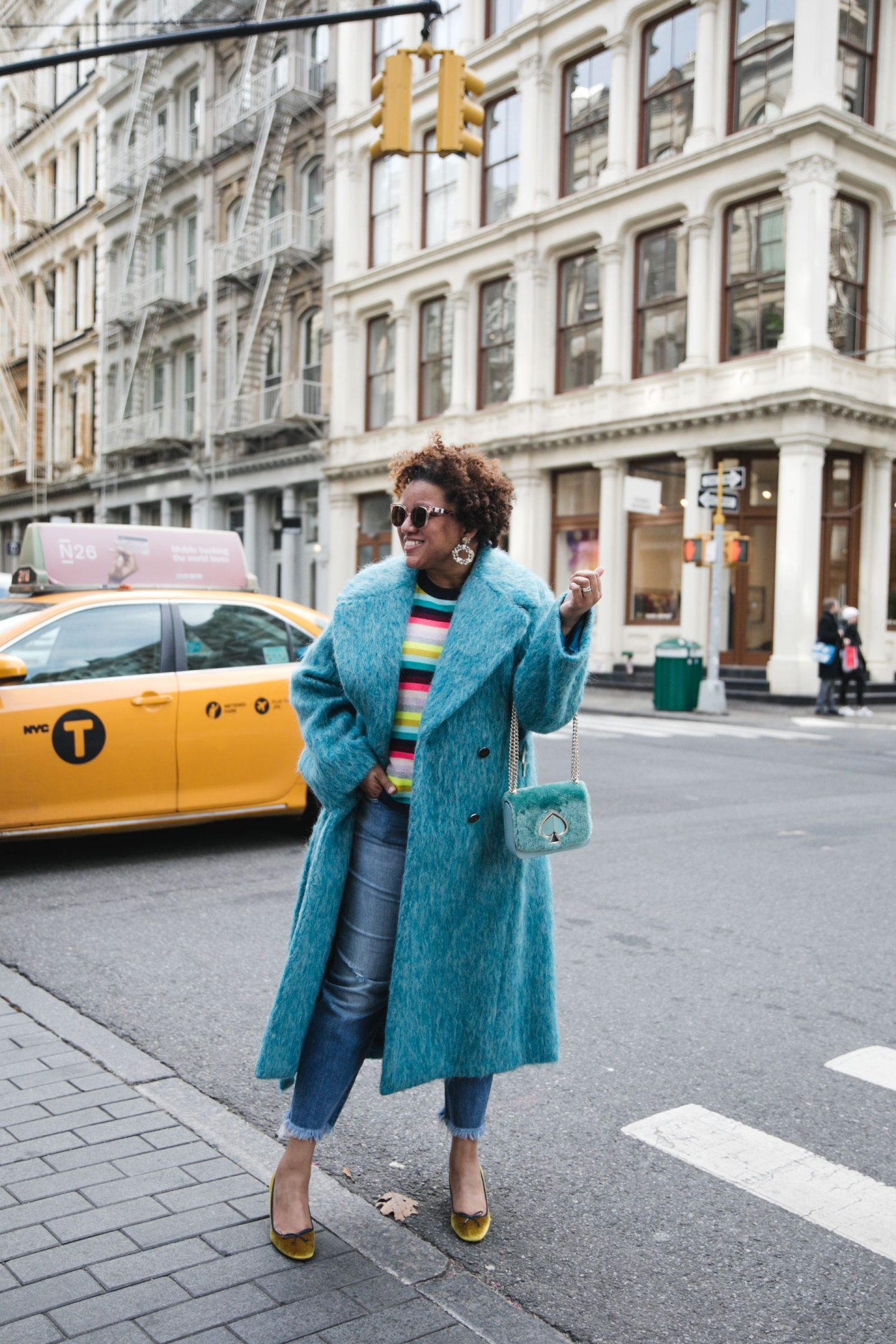 Current Favorites by popular Kentucky fashion blog, Really Rynetta: image of a woman wearing a blue fuzzy coat, gold velvet pumps, jeans, and multi color stripe sweater.