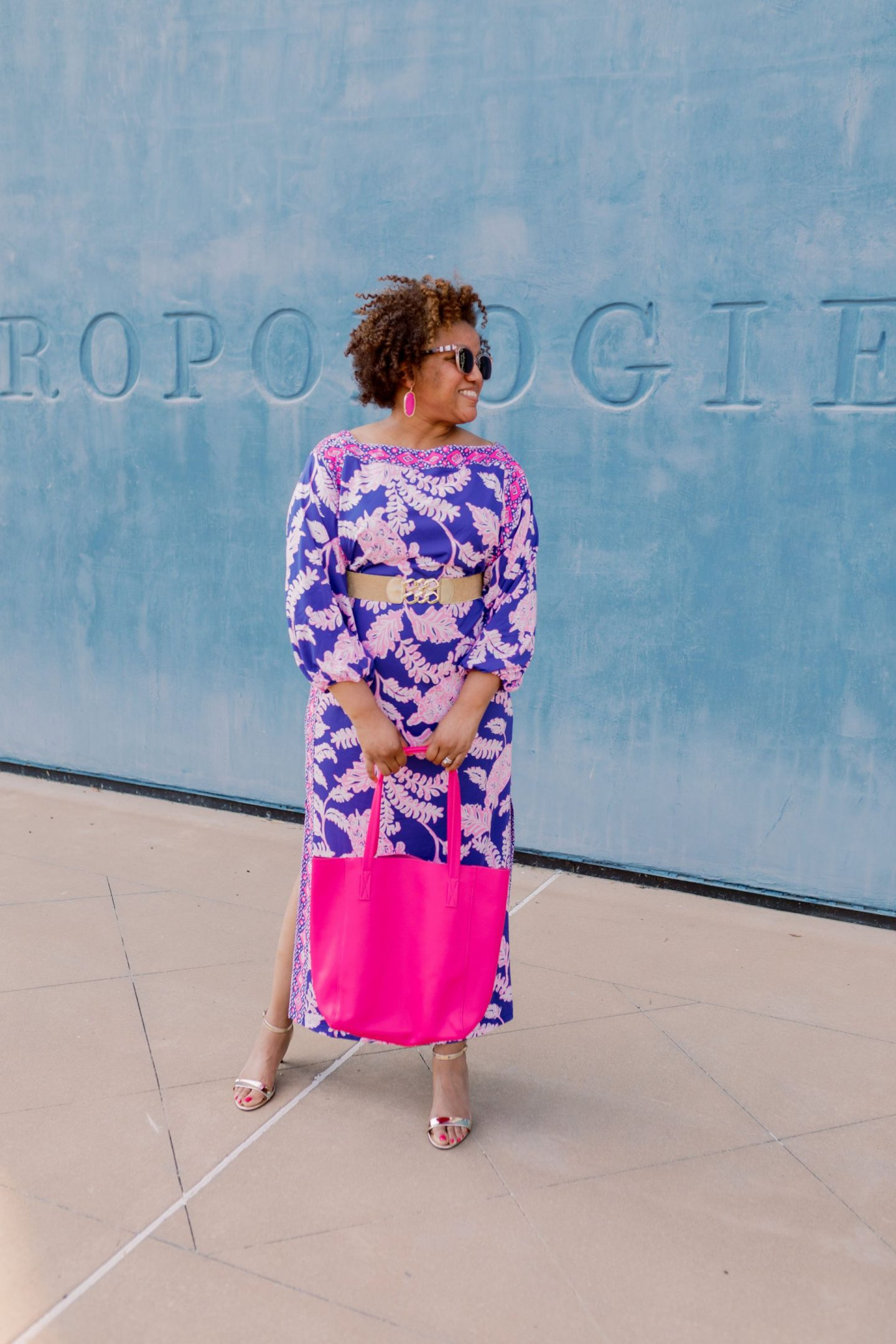 Lilly Pulitzer Dress by popular Kentucky fashion blog, Really Rynetta: image of a woman standing in front of a blue wall and wearing a Lilly Pulitzer Silva Maxi Dress, Bianca Stretch Belt, J. Crew The carryall tote, and Kendra Scott earrings.