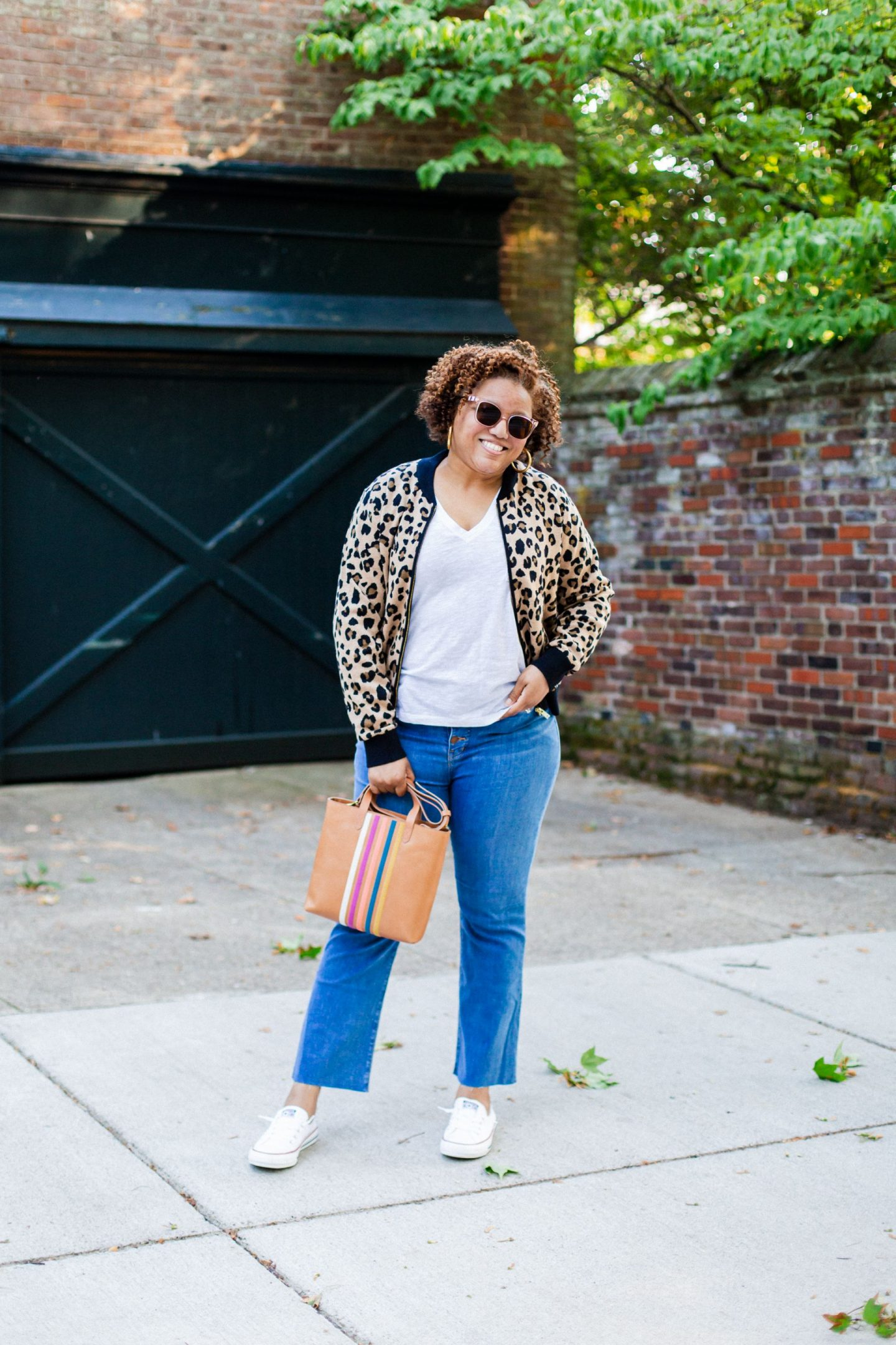 Nordstrom Favorites featured by top KW fashion blogger, Really Rynetta: image of a woman wearing a leopard bomber sweater and Madewell Cali High Waist Demi Boot Jeans | Nordstrom Fashion by popular Kentucky fashion blog, Really Rynetta: image of a woman standing outside and wearing a Nordstrom Leopard Bomber Sweater Jacket J.CREW, Nordstrom Cali High Waist Demi Boot Jeans MADEWELL, Nordstrom Whisper Cotton V-Neck Pocket Tee MADEWELL, Nordstrom Chuck Taylor® Shoreline Sneaker CONVERSE, and Nordstrom Oversized Hoop Earrings MADEWELL.