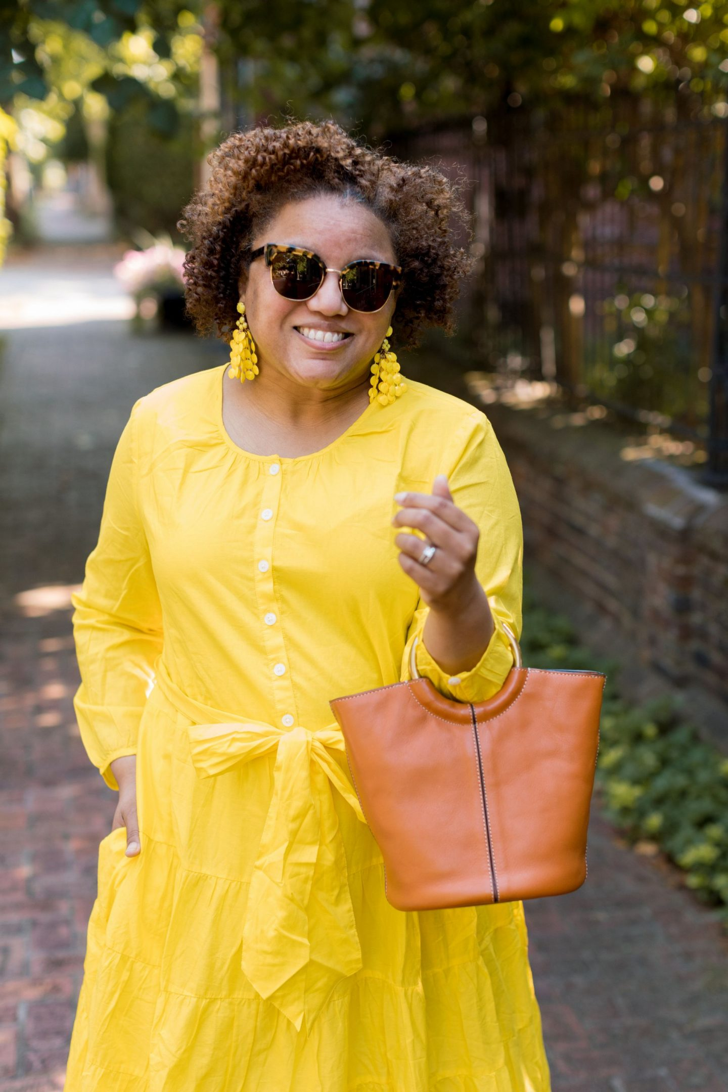 Bold Colors by popular Kentucky fashion blog, Really Rynetta: image of a woman walking outside and wearing a J. Crew Belted button-up maxi dress, Kate Spade citrus slide sandals, and carrying a Kate Spade picnic pineapple crossbody.