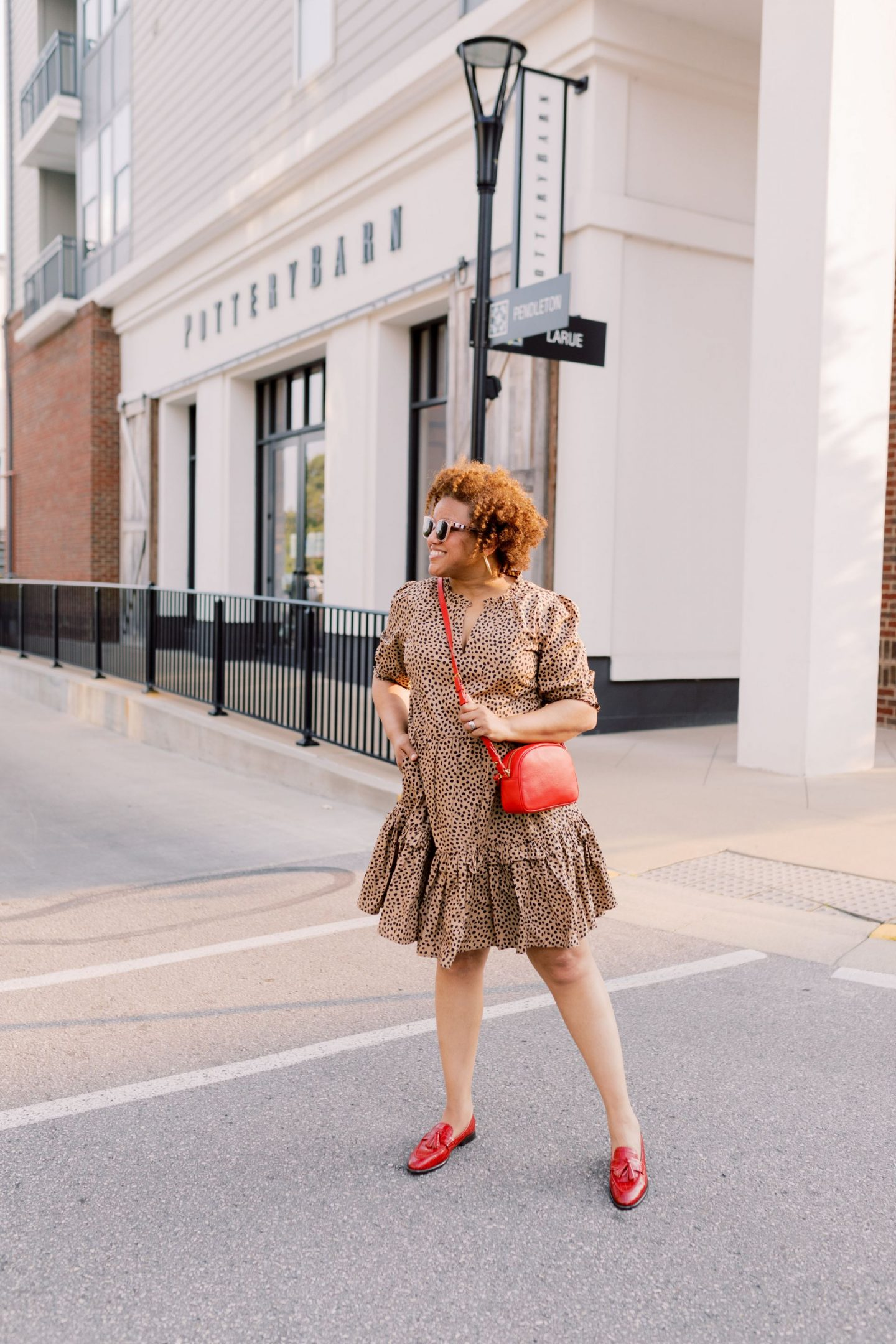 Red Loafers by popular Kentucky fashion blog, Really Rynetta: image of a woman wearing a J. Crew Ruffleneck tiered popover dress in leopard dot, J.Crew Academy loafers with tassels, Madewell Chunky Large Hoop Earrings MEDIA, and carrying a J. Crew Devon camera bag with detachable strap.