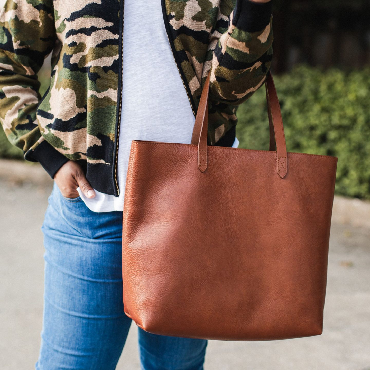Fall Clothing by popular Kentucky fashion blog, Really Rynetta: image of a woman sitting on a curb and wearing a Nordstrom camouflage sweater bomber, Nordstrom white v-neck t-shirt, white Converse sneakers, Nordstrom crop jeans, and Nordstrom leather tote.