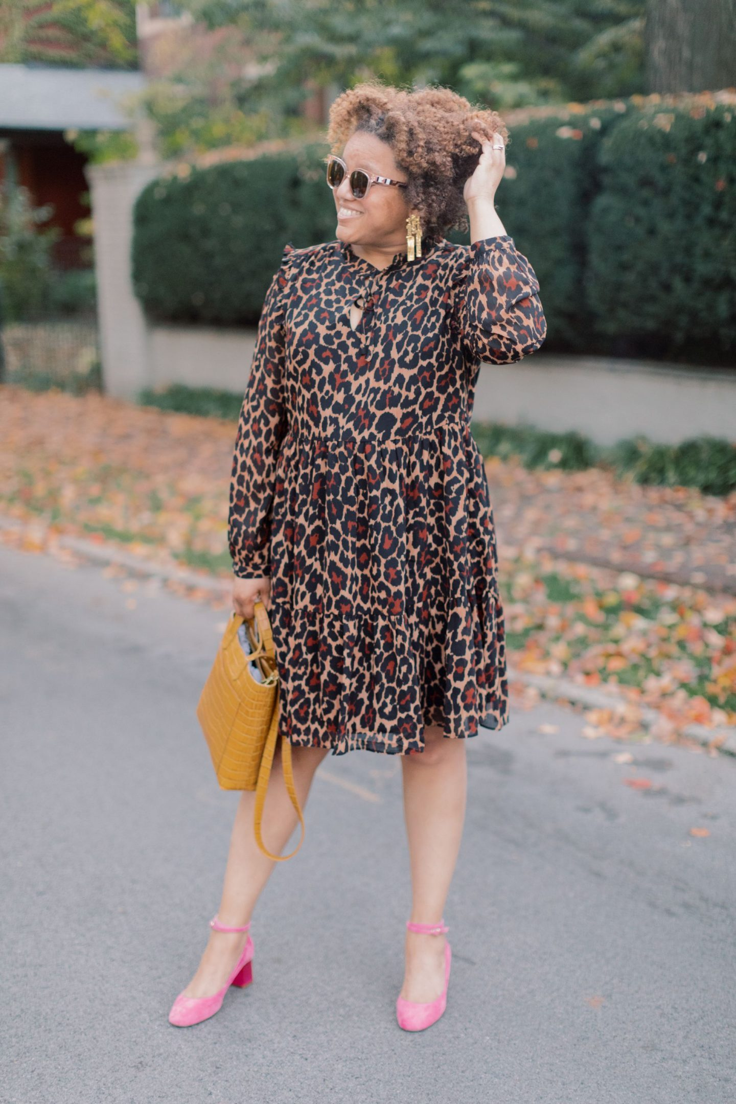 Leopard Print Clothing by popular Kentucky fashion blog, Really Rynetta: image of a woman wearing a J.Crew Tie-neck tiered dress in leopard crinkle chiffon, pink suede block heel Mary Jane shoes, Kendra Scott Holland Statement Earrings, and holding a Madewell The Small Transport Crossbody: Woven Leather Edition.