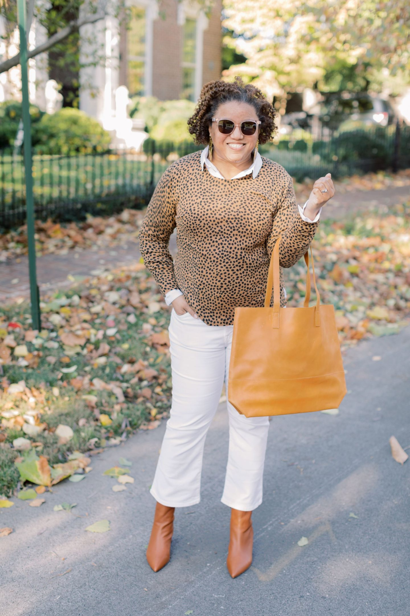 Wearing White After Labor Day by popular Kentucky fashion blog, Really Rynetta: image of a woman wearing a pair of Madewell Cali Demi-Boot Jeans in Pure White, white button up shirt, J. Crew Pointed-toe Sadie boots in leather, Kendra Scott Holland Statement Earrings, leopard print sweater, and holding a Able MAMUYE CLASSIC TOTE.
