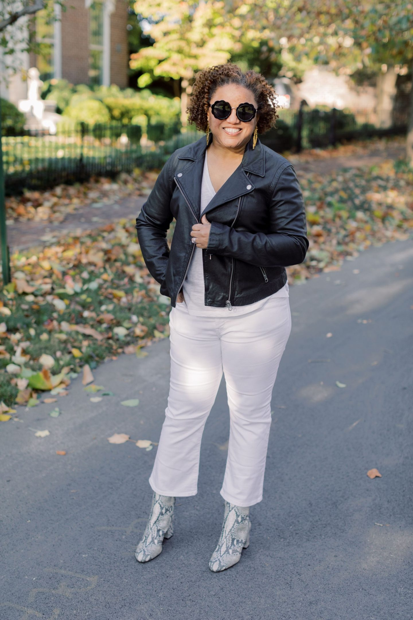 Wearing White After Labor Day by popular Kentucky fashion blog, Really Rynetta: image of a woman wearing a pair of Madewell Cali Demi-Boot Jeans in Pure White, black leather jacket, black round frame sunglasses, white t-shirt, and snake skin ankle boots.