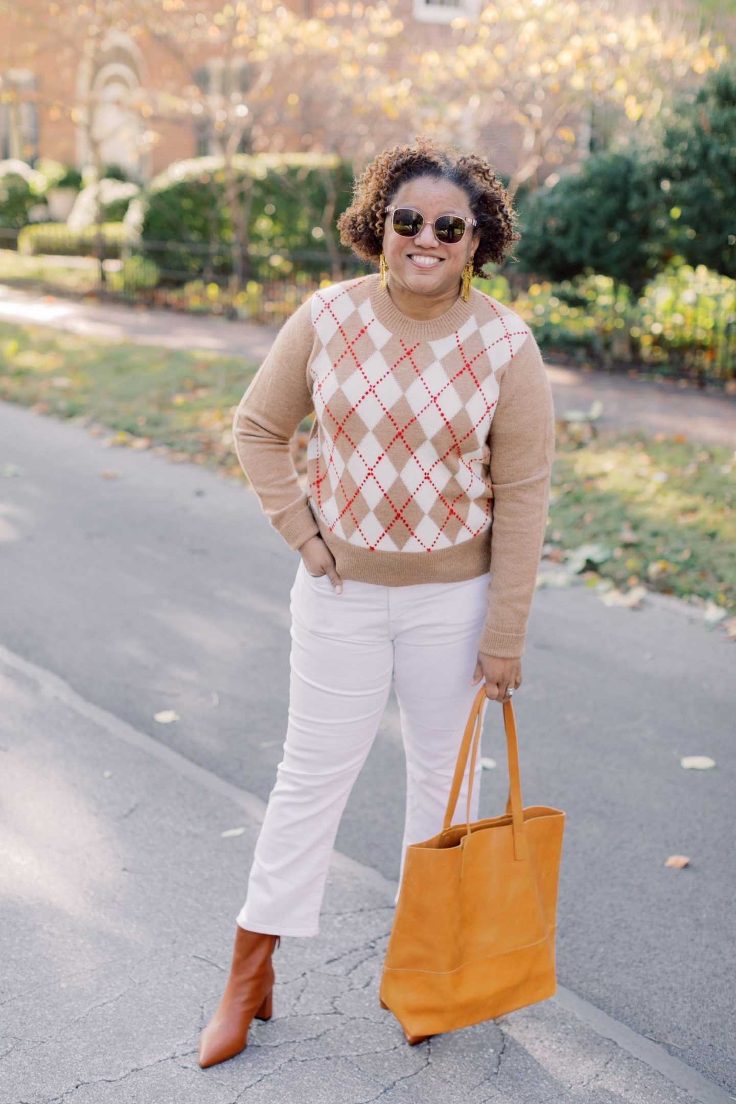 Fall Sweaters by popular Kentucky fashion blog, Really Rynetta: image of a woman wearing a J. Crew argyle sweater, Madewell Cali Demi-Boot Jeans in Pure White, Kendra Scott Holland Statement Earrings In Vintage Gold, J. Crew Pointed-toe Sadie boots in leather, and holding a leather tote bag.