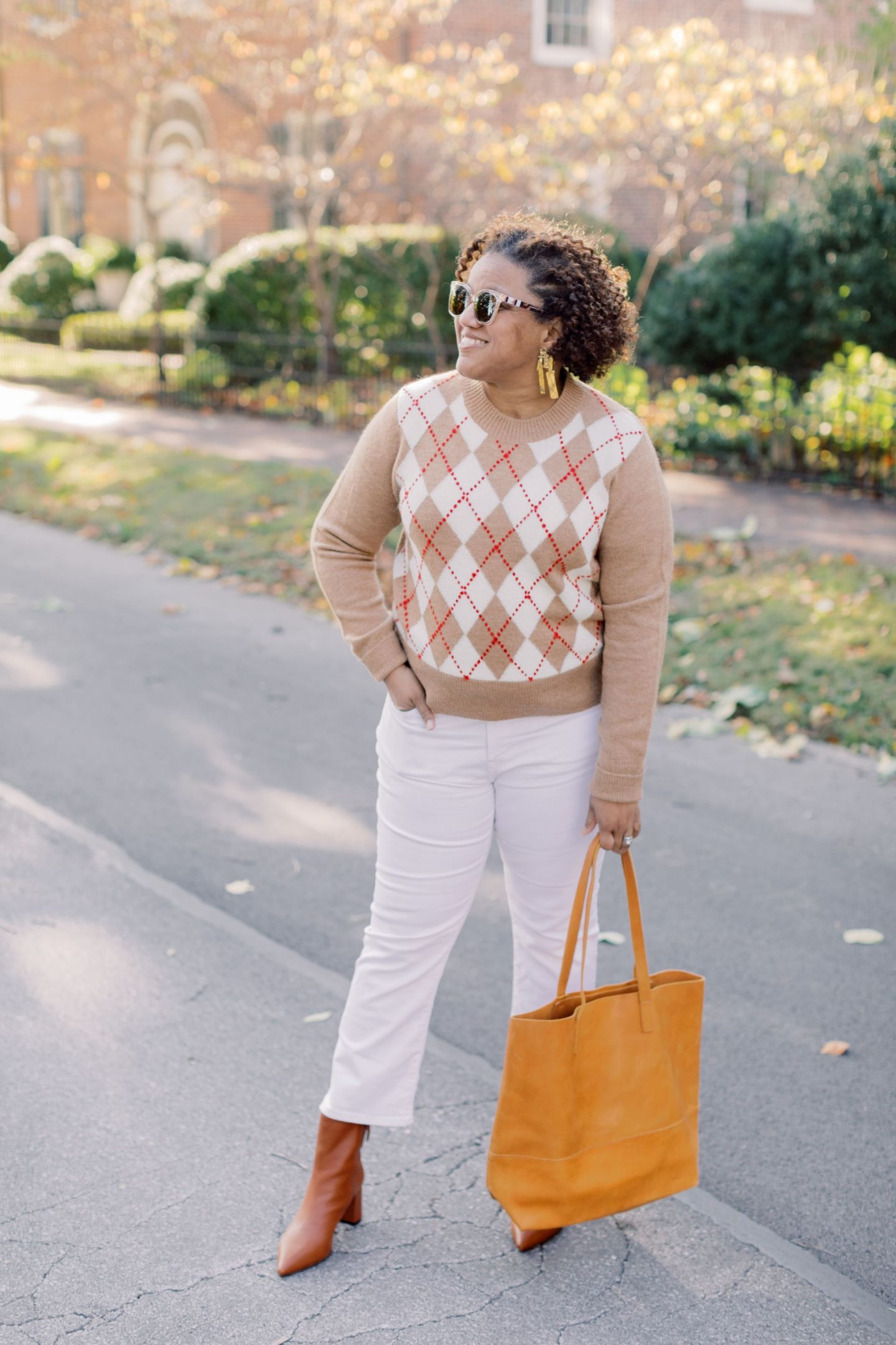 Wearing White After Labor Day by popular Kentucky fashion blog, Really Rynetta: image of a woman wearing a pair of Madewell Cali Demi-Boot Jeans in Pure White, white button up shirt, J. Crew Pointed-toe Sadie boots in leather, Kendra Scott Holland Statement Earrings, J. Crew Argyle cropped crewneck sweater, and holding a Able MAMUYE CLASSIC TOTE.