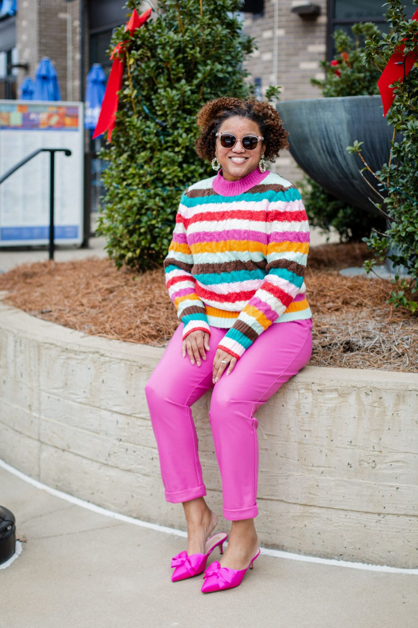 Pink Clothing by popular Kentucky fashion blog, Really Rynetta: image of a woman wearing a multi color stripe sweater with pink pants, and pink bow embellished kitten heels.