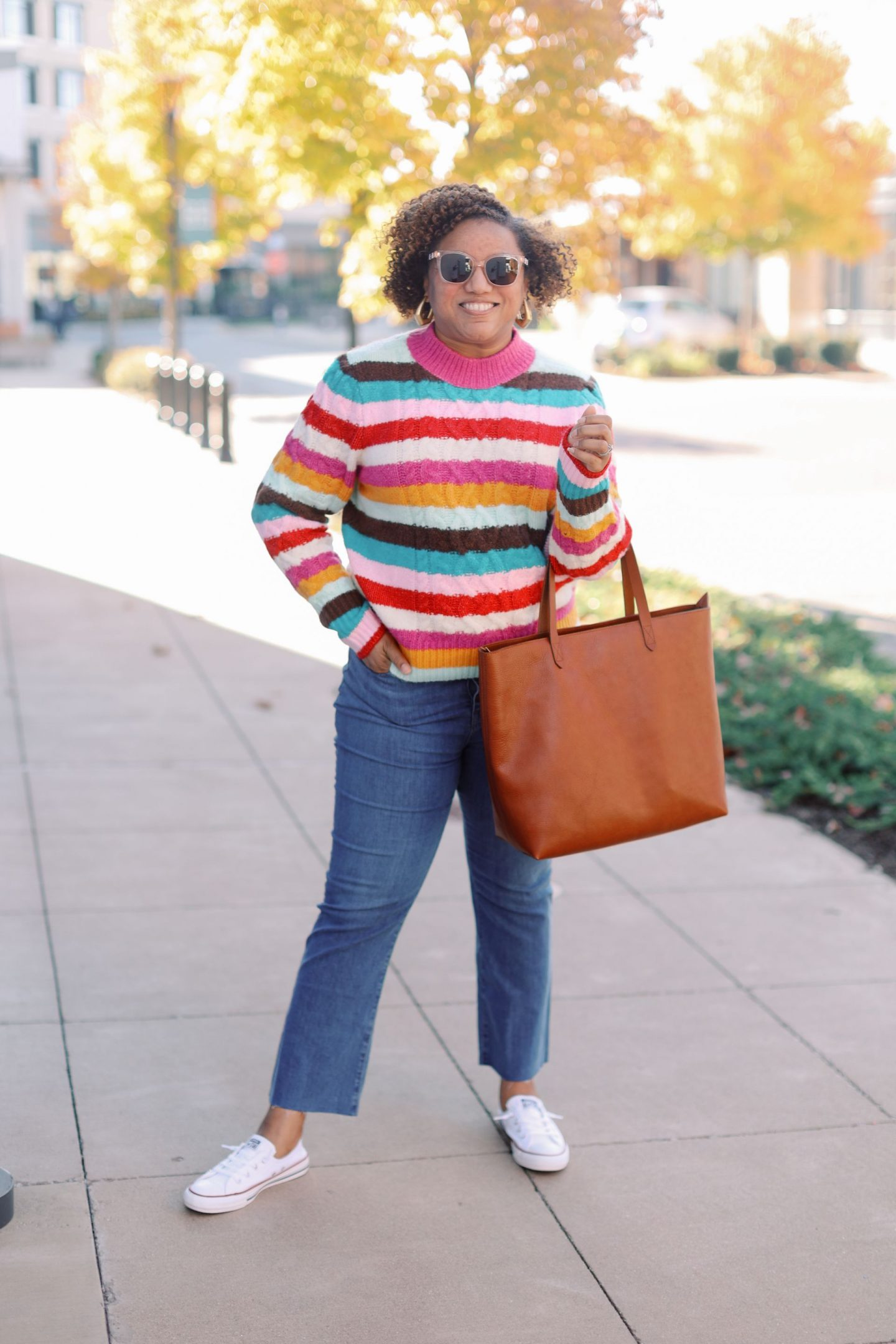 Pink Clothing by popular Kentucky fashion blog, Really Rynetta: image of a woman wearing a colorful stripe sweater, jeans, white converse sneakers, and holding a brown leather tote.