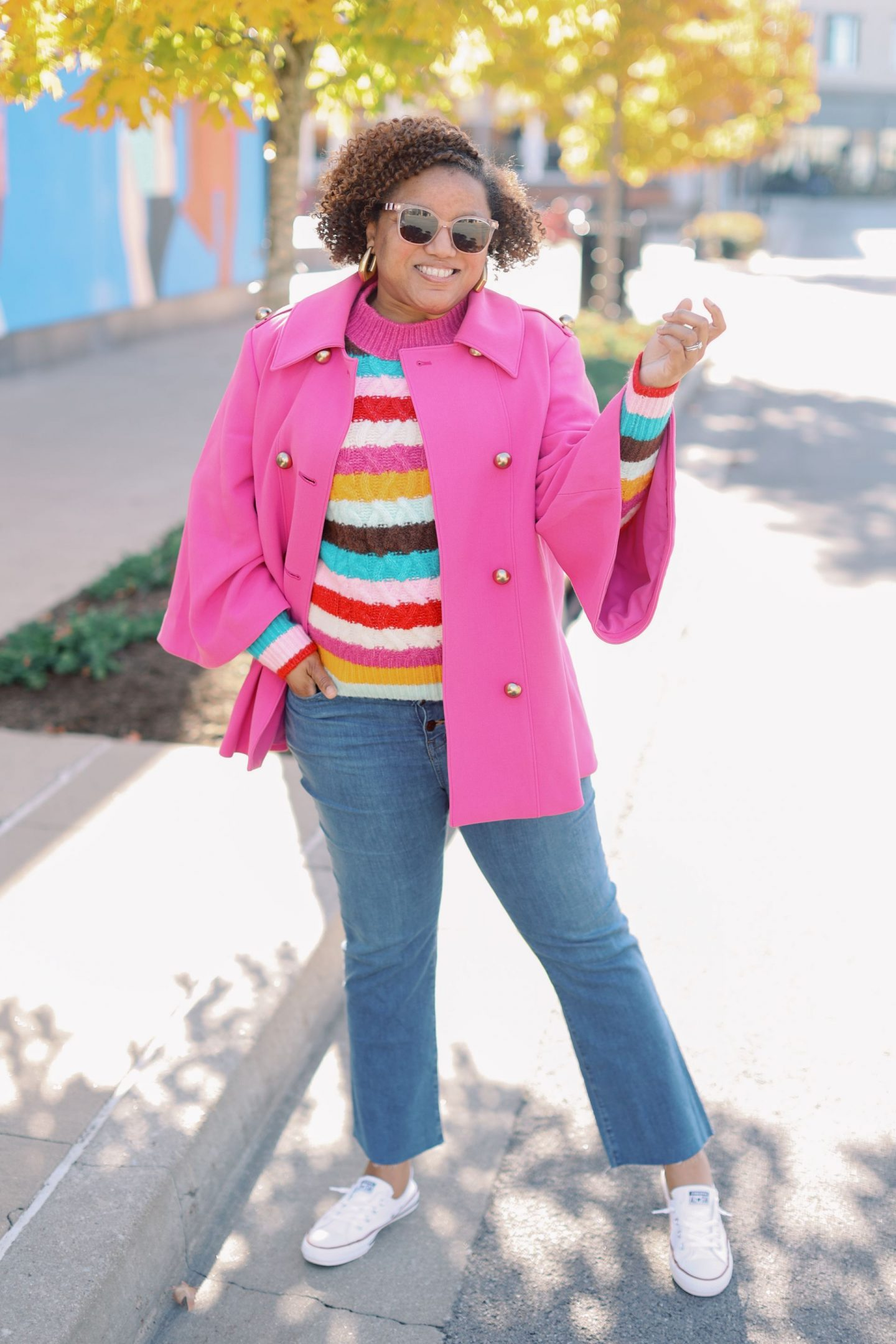Pink Clothing by popular Kentucky fashion blog, Really Rynetta: image of a woman wearing a colorful stripe sweater, jeans, white converse sneakers, and pink cape.