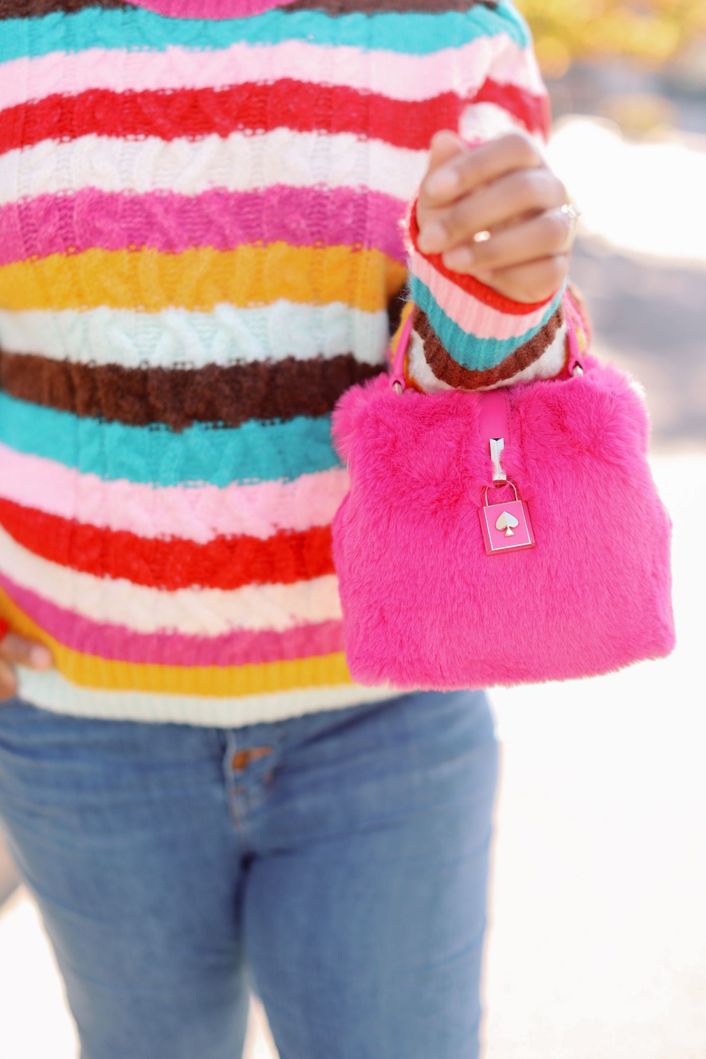 Pink Clothing by popular Kentucky fashion blog, Really Rynetta: image of a woman wearing a colorful stripe sweater, jeans, white converse sneakers, and holding a pink Kate Spade purse.