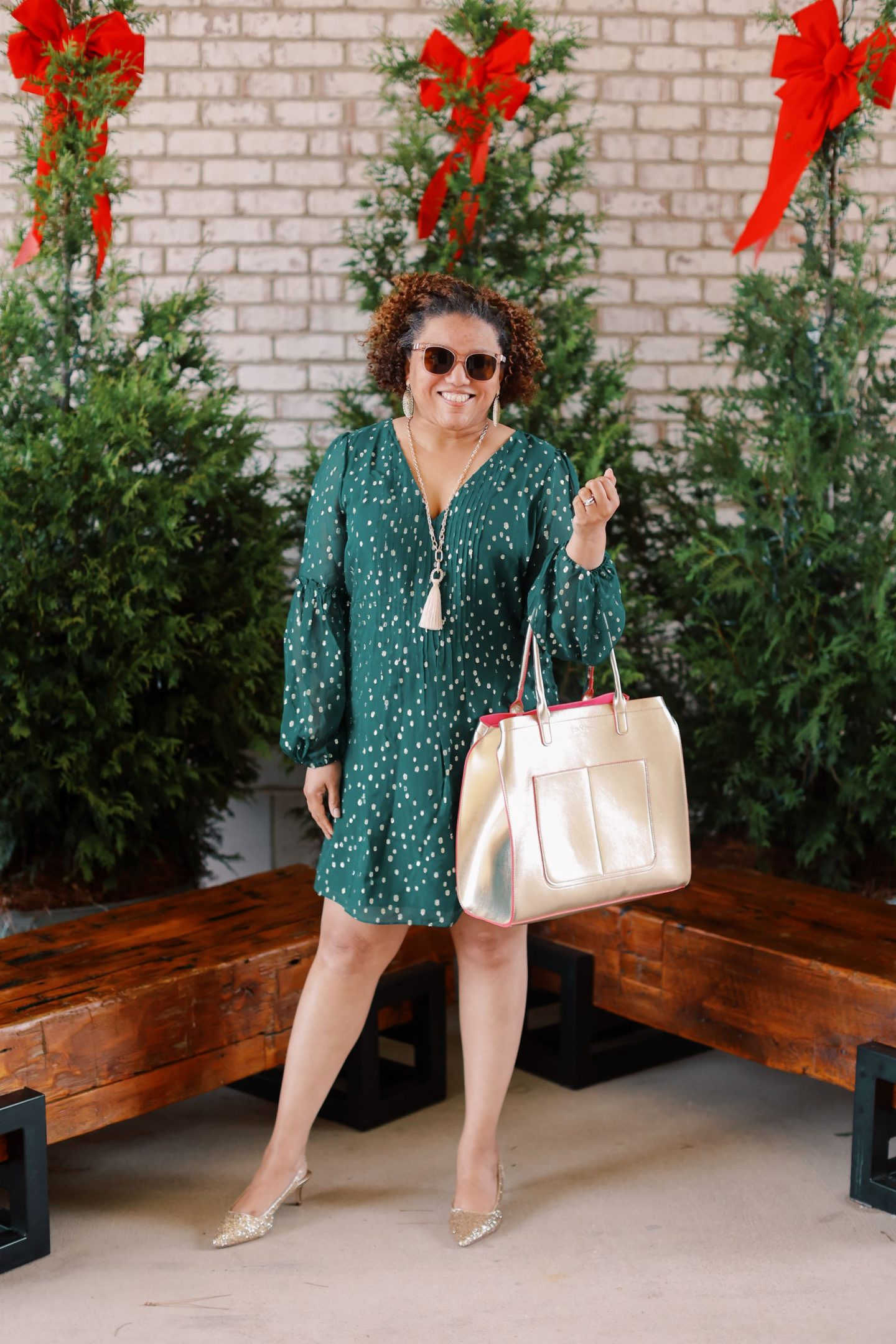 Friday Faves by popular Kentucky fashion blog, Really Rynetta: image of a woman standing in front of some pine trees and wearing a Lilly Pulitzer Cleme Silk Dress, Lilly Pulitzer Shaina Slingback Glitter Heel, Lilly Pulitzer Lilly Lace Statement Earrings, and holding a gold tote bag.