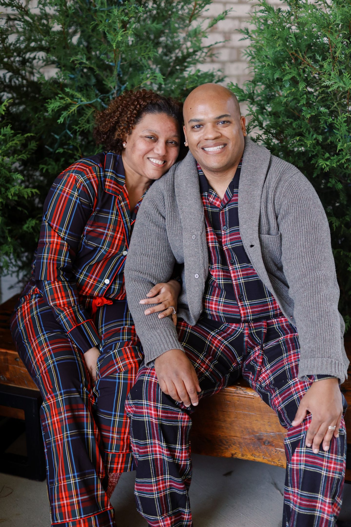 J Crew Pajamas by popular Kentucky fashion blog, Really Rynetta: image of a man and woman sitting next to each next to some pine trees and wearing a J Crew Vintage pajama set in Stewart tartan.