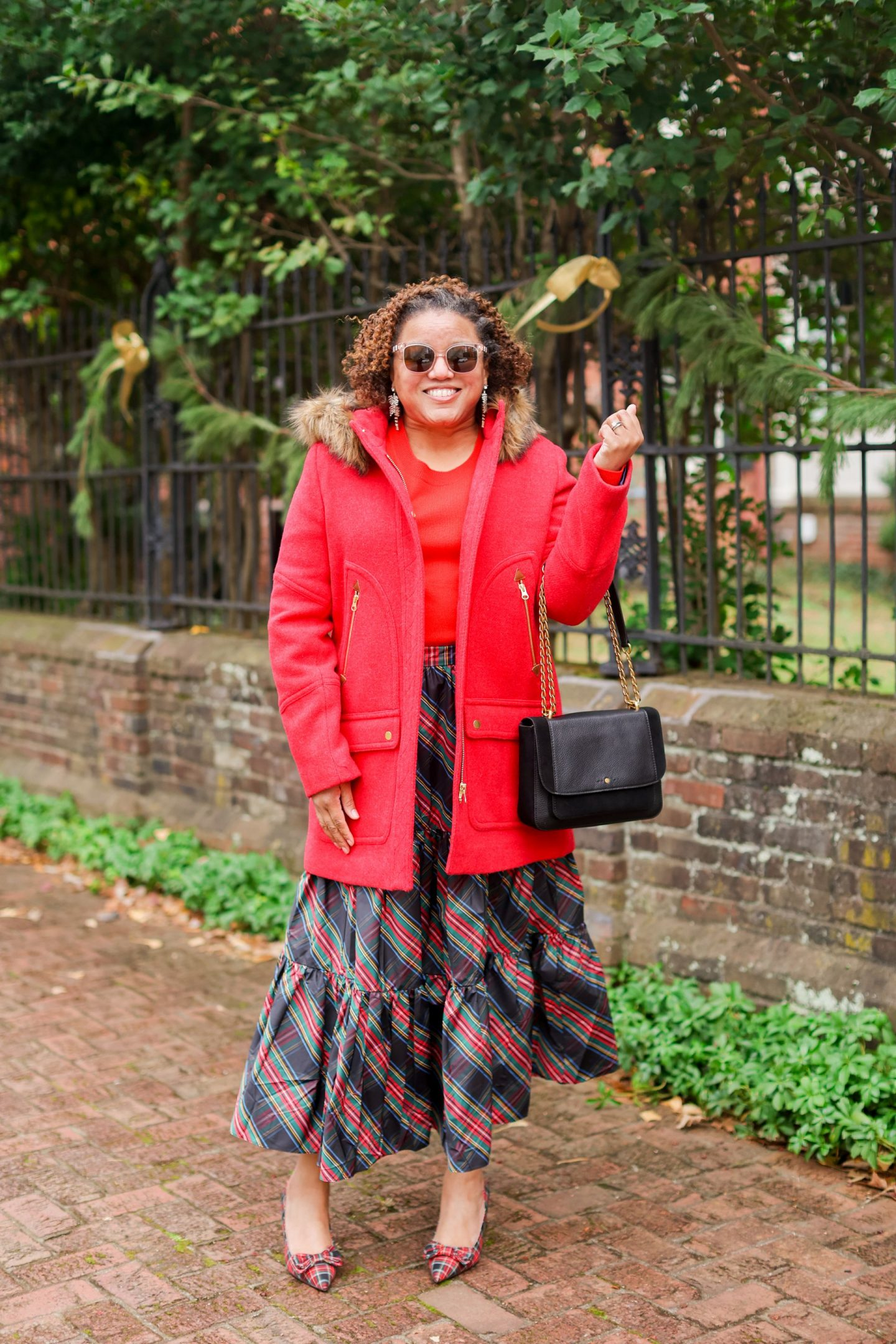 Holiday Outfits by popular Kentucky fashion blog, Really Rynetta: image of a woman standing outside and wearing a tartan plaid maxi skirt, red shirt, and chateau parka.