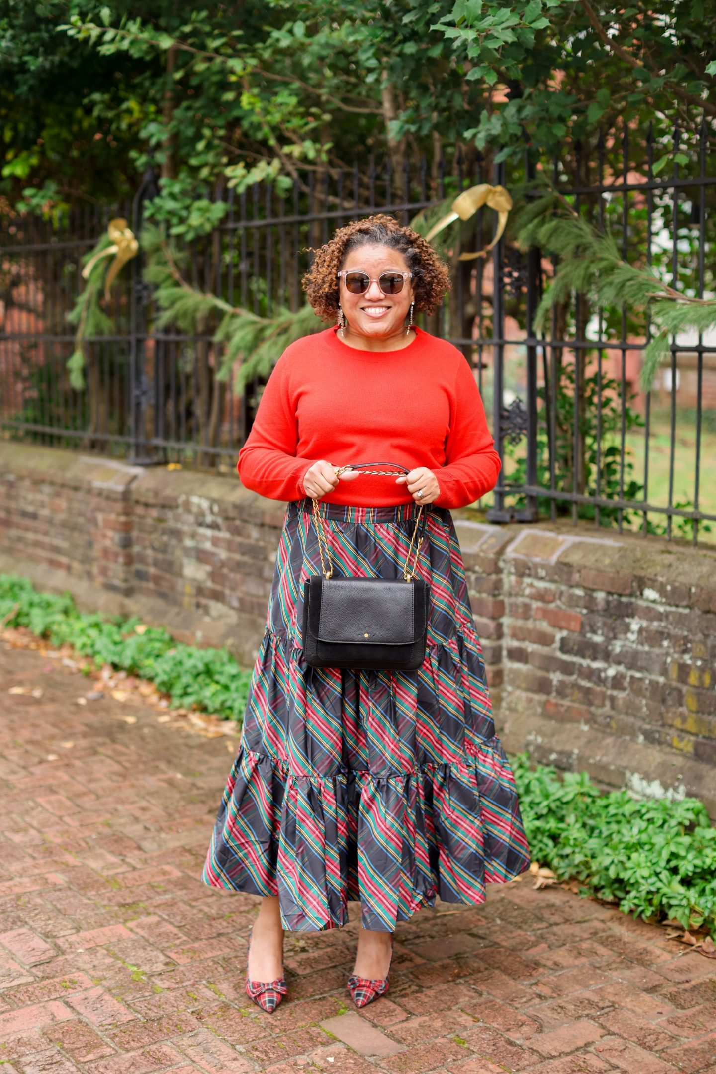 Holiday Outfits by popular Kentucky fashion blog, Really Rynetta: image of a woman standing outside and wearing a tartan plaid maxi skirt, red shirt, and tartan plaid bow embellished shoes.