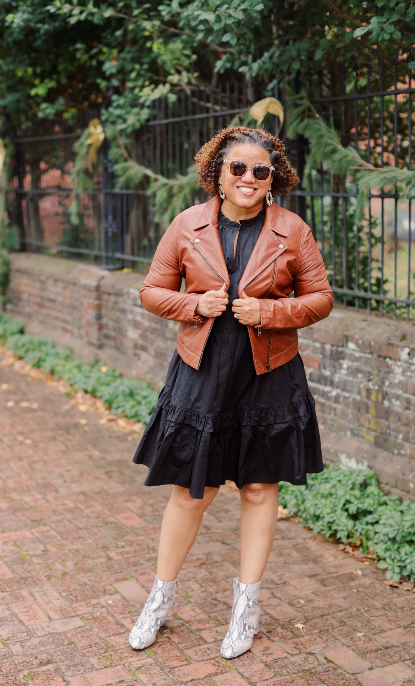 Leather Jackets by popular Kentucky fashion blog, Really Rynetta: image of a woman wearing a brown leather jacket with a black midi dress and snake skin ankle boots.