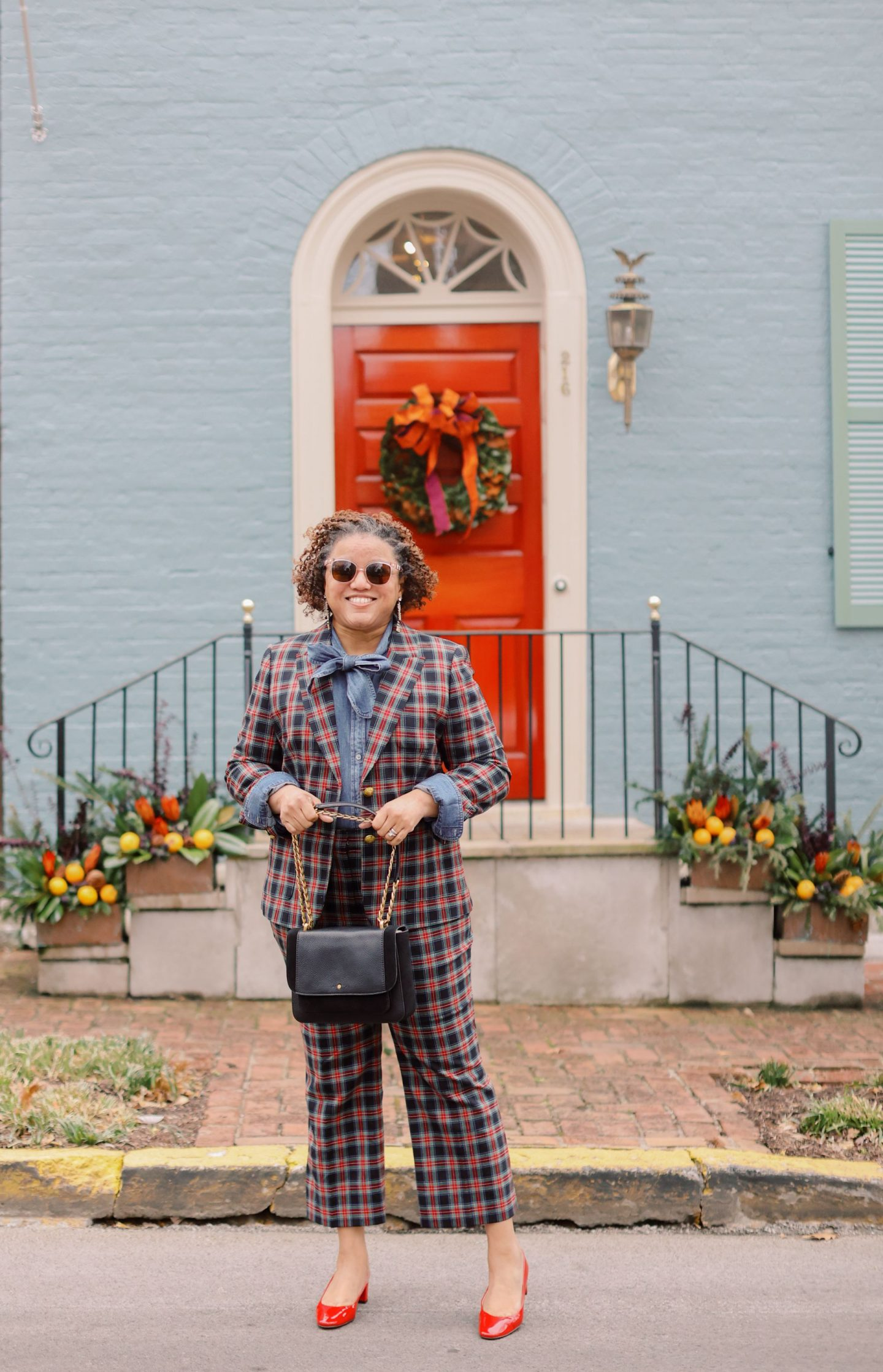 Holiday Outfits by popular Kentucky fashion blog, Really Rynetta: image of a woman standing outside and wearing a tartan plaid suit with a denim shirt and red slingback pumps.
