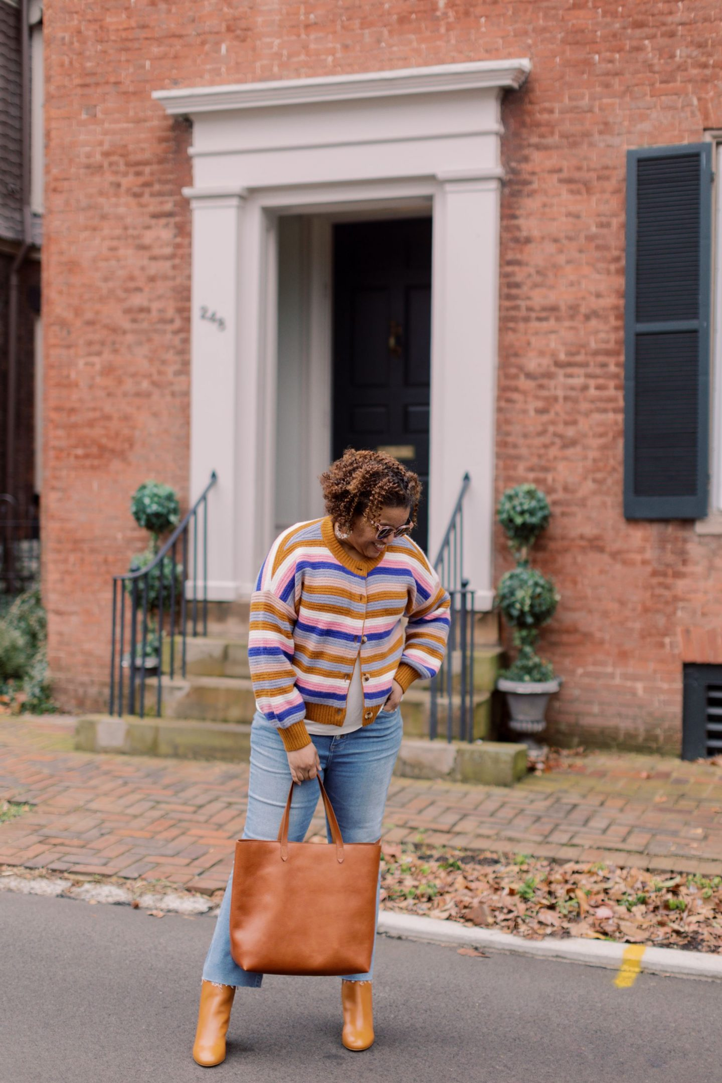 Madewell New Arrivals by popular Kentucky fashion blog, Really Rynetta: image of a woman standing outside in front of a red brick building and wearing a Madewell Striped Springview Cardigan Sweater in Coziest in Yarn, Madewell bootcut jeans, Madewell ankle boots, and holding a brown leather tote.