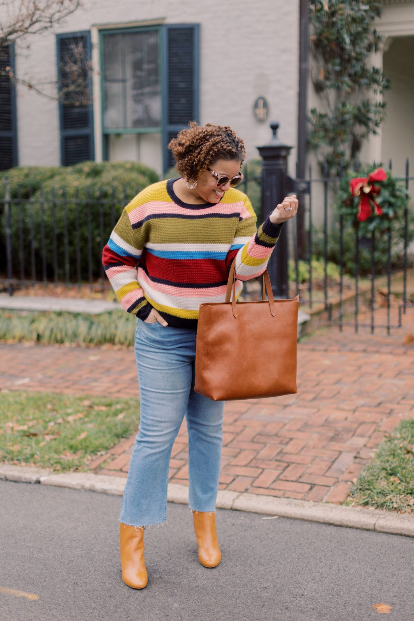 Colorful Sweaters by popular Kentucky fashion blog, Really Rynetta: image of a woman standing outside and wearing a J. Crew Cashmere Waffle-Knit Sweater in Stripe, cropped denim, brown leather ankle boots, and holding a brown leather tote.