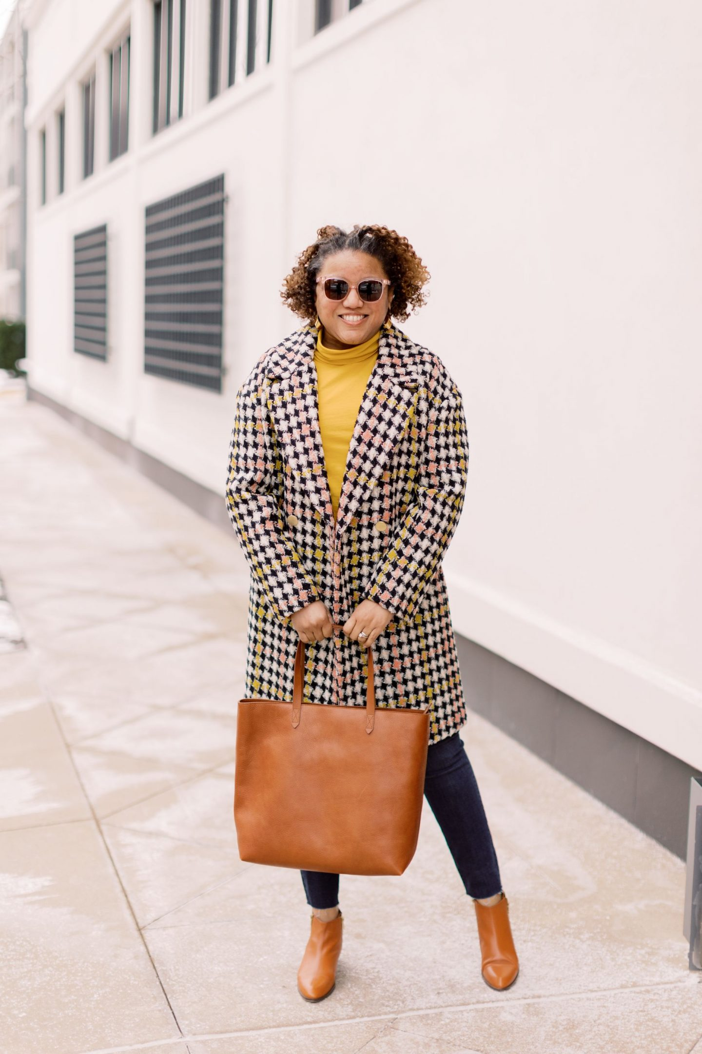 Cute Coats by popular Kentucky fashion blog, Really Rynetta: image of a woman wearing a J. Crew Tissue Turtleneck, gold statement earrings, sunglasses, skinny jeans, brown ankle boots, and a black, white, pink and yellow houndstooth coat.