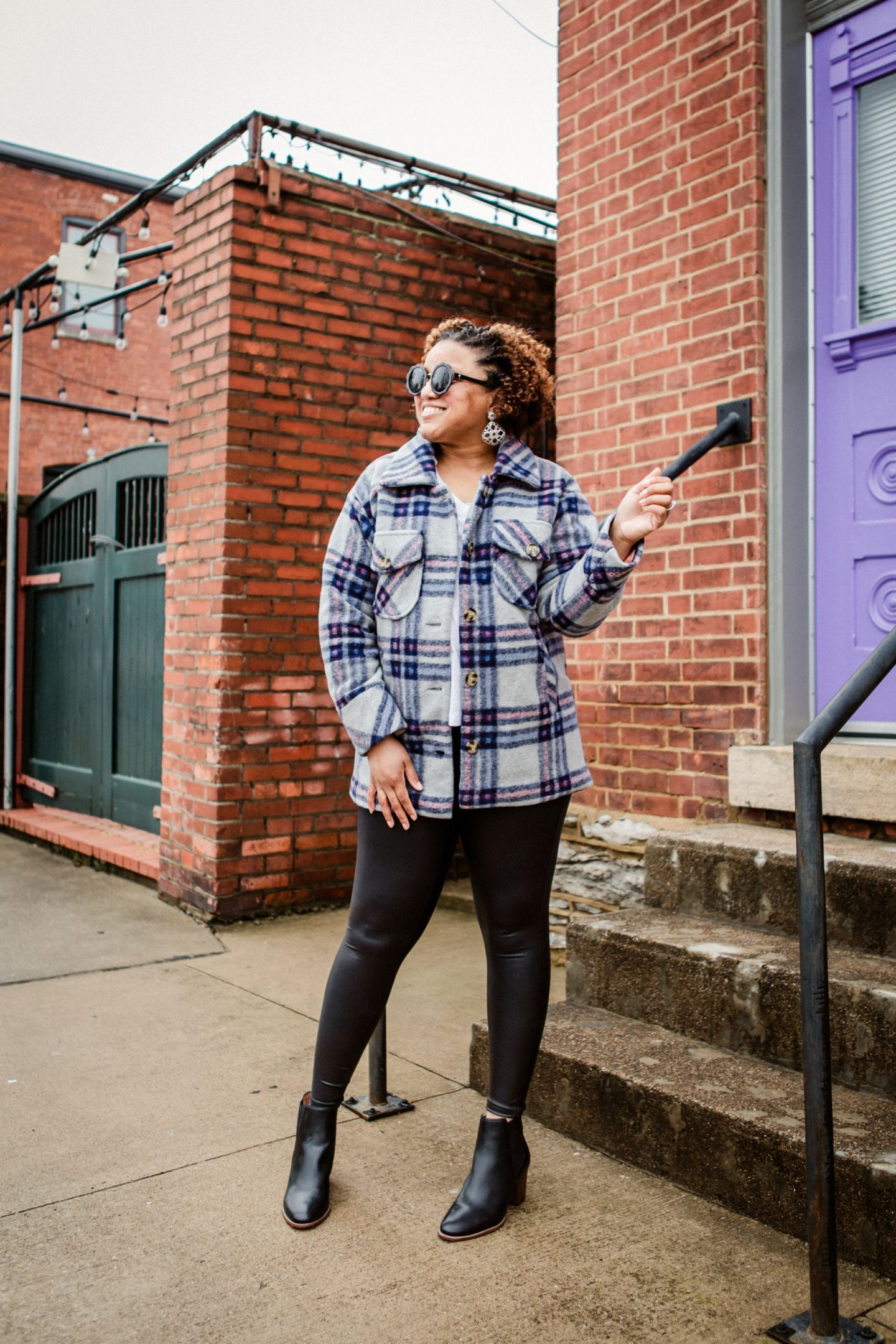 Plaid Shackets by popular Kentucky fashion blog, Really Rynetta: image of a woman standing in front of a brick building with a purple door and wearing a plaid shacket with a white t-shirt and faux leather leggings.