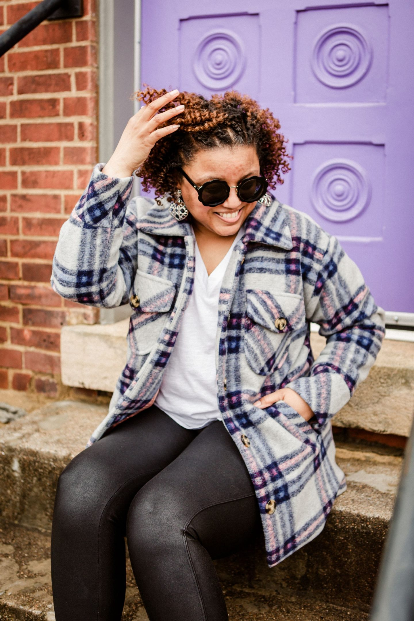 Plaid Shackets by popular Kentucky fashion blog, Really Rynetta: image of a woman sitting in front of a brick building with a purple door and wearing a plaid shacket with a white t-shirt and faux leather leggings.